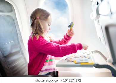 Child in airplane. Kid in air plane sitting in window seat. Flight entertainment for kids. Traveling with young children. Kids fly and travel. Family summer vacation. Girl with toy in airplane.