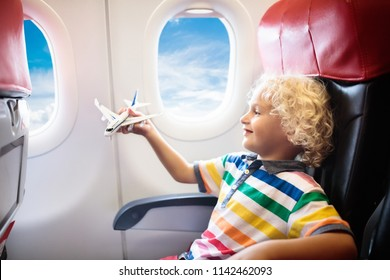 Child in airplane. Kid in air plane sitting in window seat. Flight entertainment for kids. Traveling with young children. Kids fly and travel. Family summer vacation. Little boy with toy in airplane.