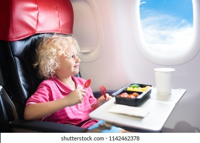 Child in airplane window seat. Kids flight meal. Children fly. Special inflight menu, food and drink for baby and kid. Little boy eating healthy lunch in airplane. Travel with kids. Family vacation.