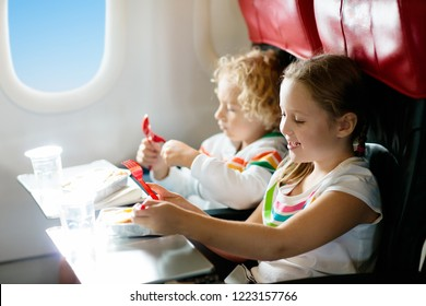 Child in airplane window seat. Kids flight meal. Children fly. Special inflight menu, food and drink for baby and kid. Girl and boy eating healthy lunch in airplane. Travel and family vacation.