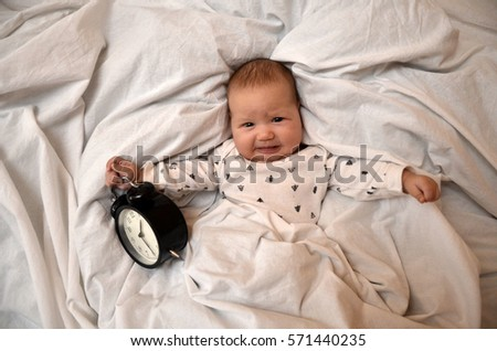 Child With An Alarm Clock Lying On The Bed And Wishes Everyone A Good Morning
