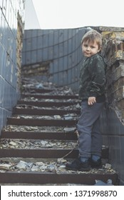 The child is alone, abandoned. Little boy on the destroyed steps of the building.
