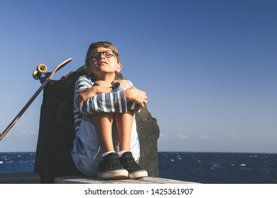 Child alone sitting near the ocean with skateboard. Sad boy crying in a sunny summer day. Kid arms crossed hold the knees. Sad lonely afternoon for a young cold boy waiting help. Concept of weakness