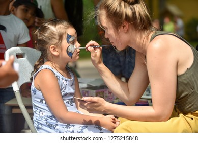 Child animator, artist's hand draws face painting to little girl. Child with funny face painting. Painter makes blue butterfly at girl's face.  Rezekne - Latvia, July 24, 2018