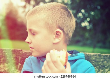 child with apple sitting on the bench