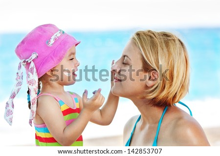 Child applying suntan  lotion to her mom and having great time together