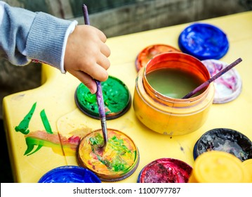 Child with an artistic brush in his hand draws and dilutes the paint close up