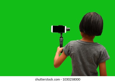 Child Asian girl holding Smartphone Gimbal Stabilizer for recording footage. Child and Technology concepts. Isolated on green background.