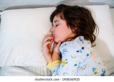 child asleep in bed with closed eyes and innocent face, wearing pajamas and white sheets