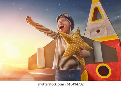 Child in astronaut costume with toy rocket playing and dreaming of becoming a spacemen. Portrait of funny kid on a background of sunset star sky on nature. Family games outdoors.