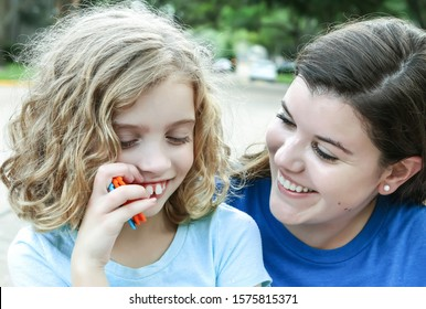 a child with autism is smiling and having fun interacting with her young relative or caregiver; they are wearing light and dark blue shirts to promote autism awareness