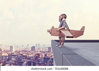 child aviator with cardboard airplane on top building
