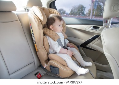 child in a baby car seat. Isofix clamping. beige car seat in a bright salon. Protection in the car.