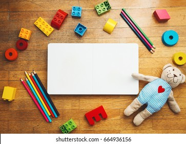 Child or baby play set with empty book or notepad, toy wooden blocks, plastic constructor, colored pencils, teddy bear. Back to school, education concept. Kindergarten or preschool background.