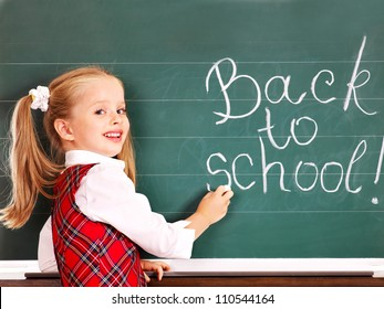 Child with backpack writting text on blackboard.