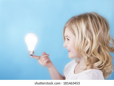 Child balancing a glowing light bulb on her finger with a blue background.