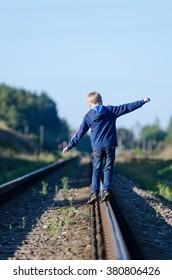 Child balancing goes on railway rails