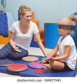 Child with a band on eyes during sensory integration therapy with occupational therapist