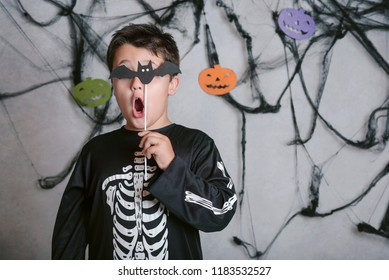 child with a bat covering his eye at halloween party