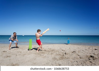 A child batting in a game of Beach Cricket.