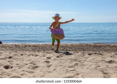 Child with beach bag on summer vacation. Happy boy running in nature with beautiful sea, sand and blue sky.