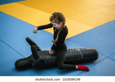 The child beats the training dummy with his hands. A little girl sits on top on a training mannequin and works off punches. Children's sports activity in the gym