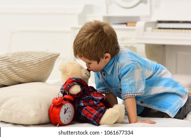 Child in bedroom kiss toy in nose. Good night concept. Boy with happy face puts favourite toy on bed, wishing sweet dreams. Kid put plush bear near pillows and alarm clock, luxury interior background.