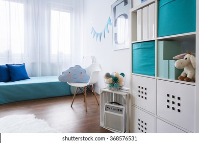 Child bedroom in light colors with bed and modern shelving unit