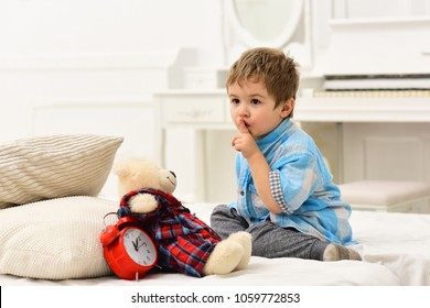 Child in bedroom with silence gesture. Boy with calm face puts favourite toy on bed, time to sleep. Kid put plush bear near pillows and alarm clock, luxury interior background. Time to sleep concept.