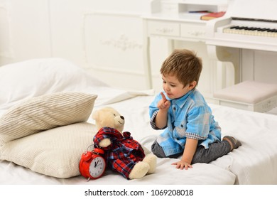 Child in bedroom with silence gesture. Time to sleep concept. Boy with happy face puts favourite toy on bed, time to sleep. Kid put plush bear near pillows and alarm clock, luxury interior background.