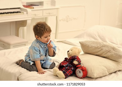 Child in bedroom with silence gesture. Time to sleep concept. Boy with happy face puts favourite toy on bed, time to sleep. Kid put plush bear near pillows and alarm clock, luxury interior background
