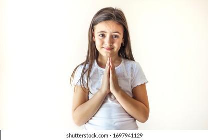 Child begging for something, making gestures of prayer, saying please with imploring eyes, having hopeful expression and wishing for something
