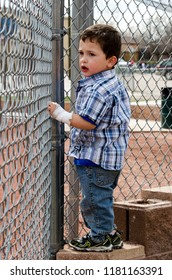 Child behind a metal fence at a baseball game