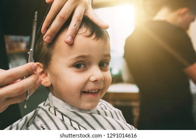 The child is being cut hairstyles in the hairdressing salon