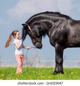 Child and big black horse in pasture.