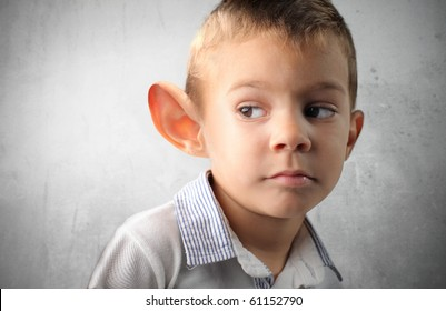 Child with big ear listening to something
