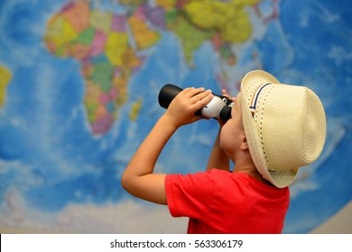 Child with binoculars is playing in travelers. Adventure and travel concept. Joyful and creative background.