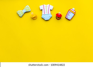 Child birth. Accessories for newborn on yellow baclground top view copy space