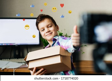 a child blogger takes pictures of himself on a camera, shows a like, holds a box in his hands, blog, video recording at home for a blog