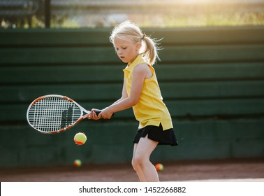 A child blond girl in a yellow polo playing tennis at the court on a sunset