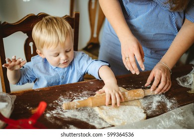A child with blond hair helps her mother in the kitchen cooking and rolls the dough, playing with flour
