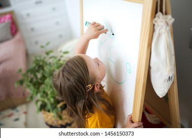 Child blonde girl with Down syndrome is painted with markers on a children's easel, a light real interior of a nursery