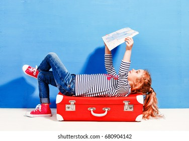 Child blonde girl with pink vintage suitcase and city map ready
