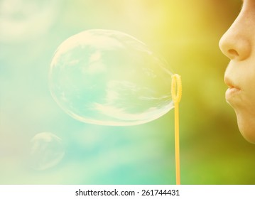 Child blowing bubbles.  Instagram effect.  Focus on lips and edge of bubble wand.