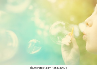 Child blowing bubbles.  Instagram effect