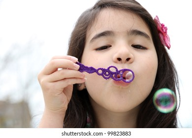Child blowing bubbles outside in the summer