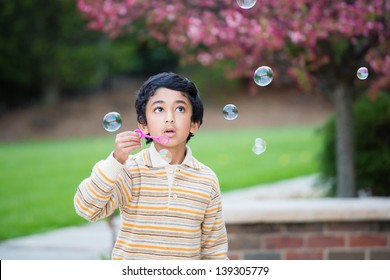 Child Blowing Bubbles in the Yard in Spring