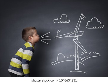 Child blowing a chalk drawing of a wind turbine on a blackboard concept for alternative renewable energy and education of the environment
