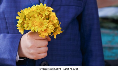Child in blue jacket with yellow bouquet. Some celebration or wedding.