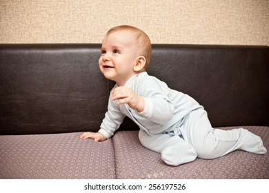 child in a blue suit crawling on the couch